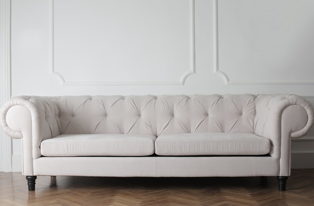 a modern white leather sofa in a white room